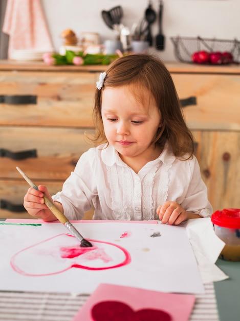 Mała Dziewczynka Maluje Czerwonego Serce Na Papierze Darmowe Zdjęcia