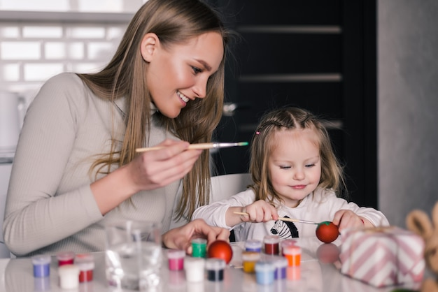 Mała Dziewczynka Maluje Easter Jajka Z Matką W Kuchni Darmowe Zdjęcia