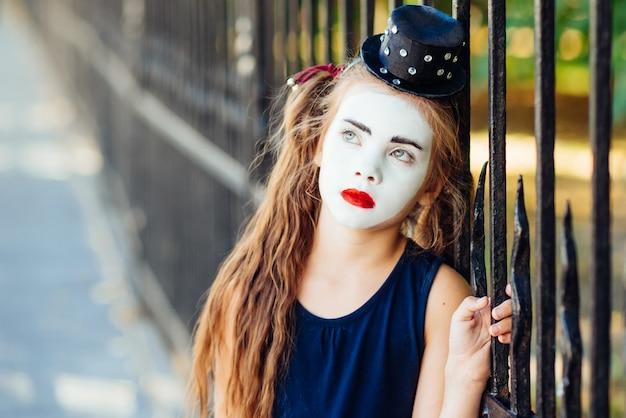 Mała dziewczynka mim jest smutną pozycją przy ogrodzeniem Premium Zdjęcia