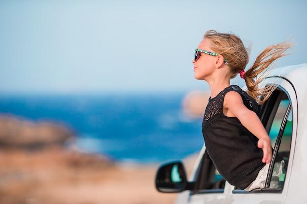 Mała dziewczynka na wakacje podróży samochodu onbeautiful krajobrazem Premium Zdjęcia