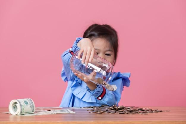 Mała dziewczynka nalewa monety z przezroczystego szklanego słoika Premium Zdjęcia