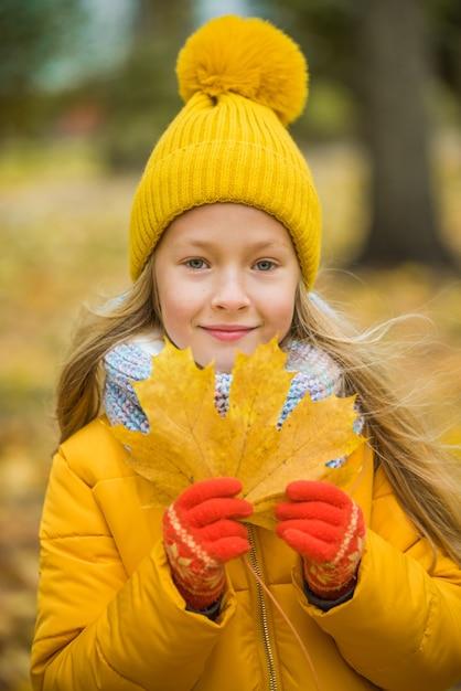 Mała Dziewczynka O Blond Włosach W Jesień Parku Z żółtym Liściem Premium Zdjęcia
