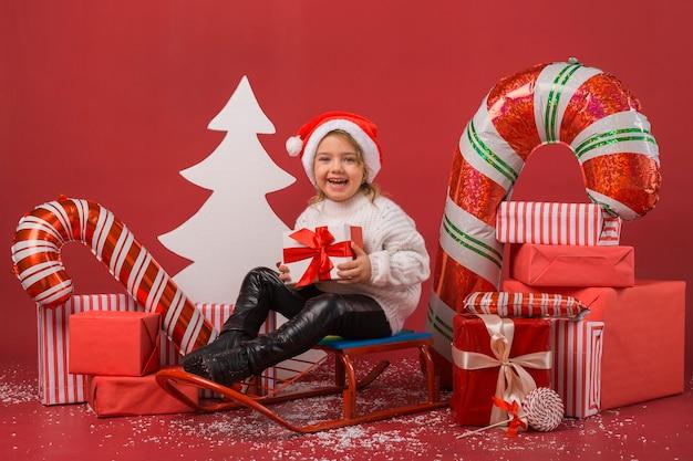 Mała Dziewczynka Otoczona Prezentami świątecznymi I Elementami Premium Zdjęcia