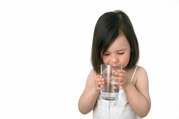 Mała dziewczynka pije wodę ze szklanego kubka. Premium Zdjęcia