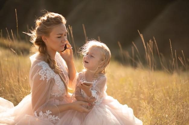 Mała Dziewczynka Płacze, Gdy Jej Mama Rozmawia Przez Telefon Premium Zdjęcia