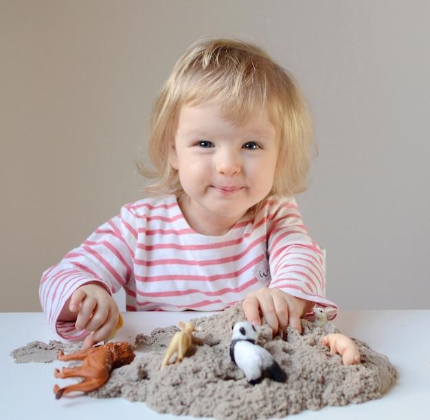 Mała dziewczynka plyaying z kinetycznym piaskiem i zabawkarskimi zwierzętami Premium Zdjęcia