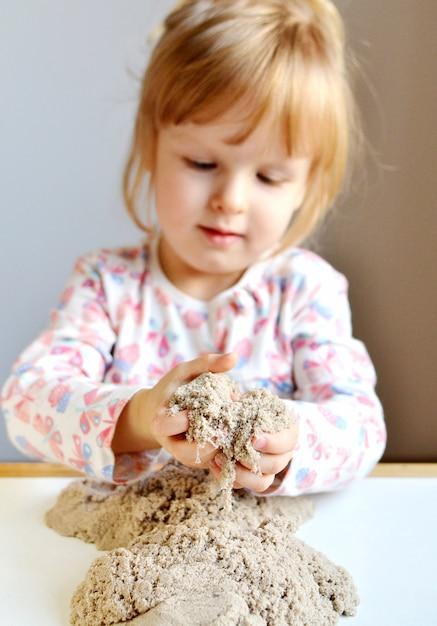 Mała dziewczynka plyaying z kinetycznym piaskiem w domu Premium Zdjęcia