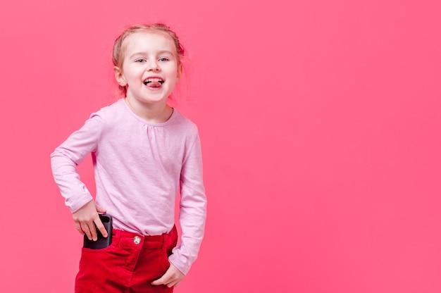 Mała Dziewczynka Pokazuje Język I Wkłada Telefon Do Kieszeni Premium Zdjęcia