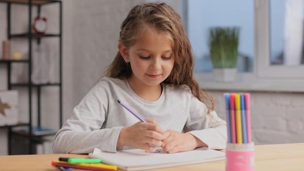 Mała Dziewczynka Rysowanie Obrazków Pisakiem Na Białej Księdze Albumu. Zabawa Sama, Twórcza Działalność Artystyczna W Domu. Premium Zdjęcia