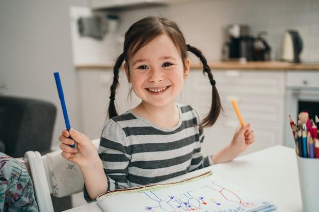 Mała Dziewczynka Rysuje Obrazek W Domu. Dziewczyna Z Dwoma Warkoczykami Uczy Się W Domu Online. Utalentowana Dziewczyna Malująca Obraz. Premium Zdjęcia