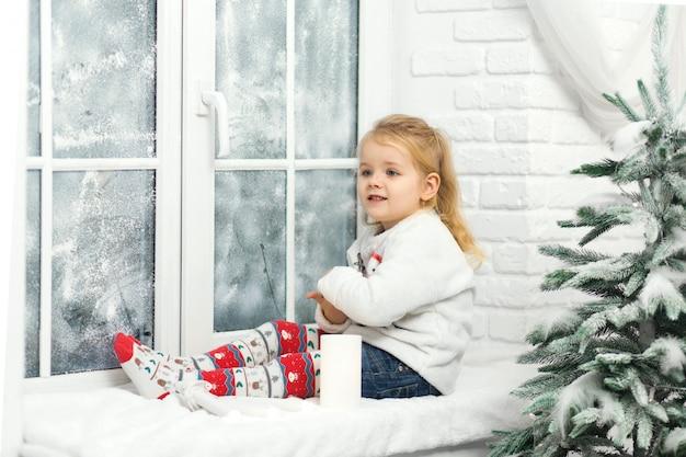 Mała Dziewczynka Siedzi Na Parapecie Wieczorem Przed świętami Bożego Narodzenia. Przytulny Romantyczny Wypad Zimą. Wesołych świąt, Nowego Roku, Wakacji, Zimy, Dzieciństwa Premium Zdjęcia