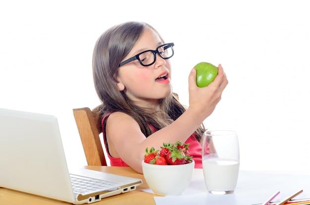 Mała Dziewczynka Siedzi Przy Biurku I Je Jabłko Premium Zdjęcia