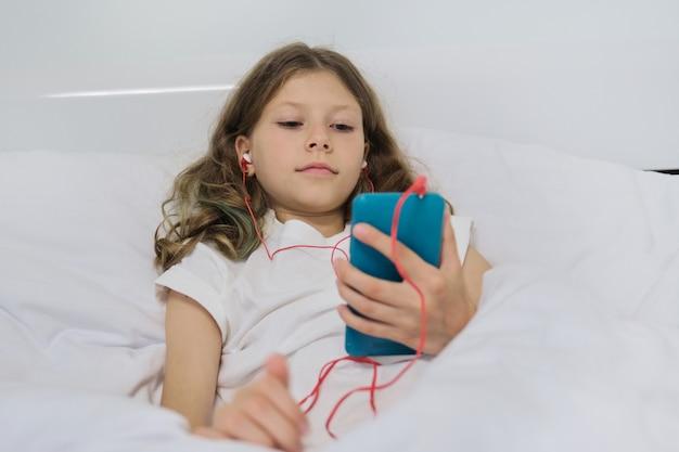 Mała Dziewczynka Siedzi W Domu W łóżku, Z Smartphone I Hełmofonami Premium Zdjęcia