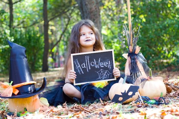 Mała Dziewczynka Siedzi W Parku Z żółtymi Liśćmi W Stroju Wiedźmy. Miotła, Dynia, Maska Nietoperza, Kapelusz Czarownicy. Halloween. Premium Zdjęcia