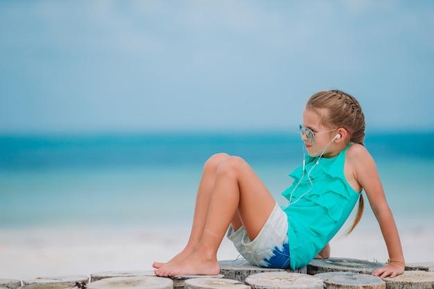 Mała Dziewczynka Słucha Muzyka Na Hełmofonach Na Karaibskiej Plaży Premium Zdjęcia
