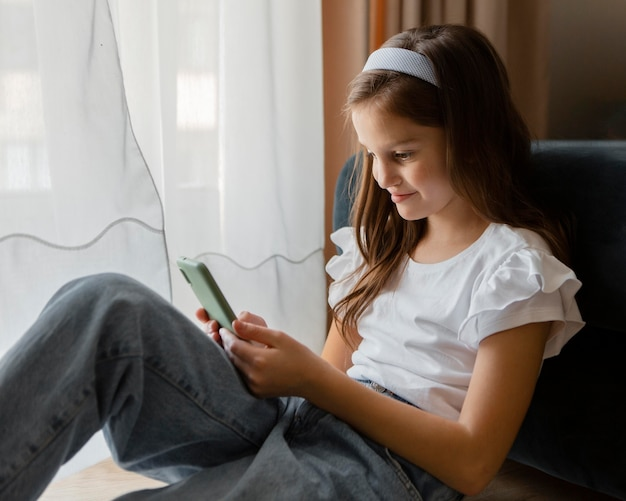 Mała dziewczynka sprawdza swój telefon Darmowe Zdjęcia