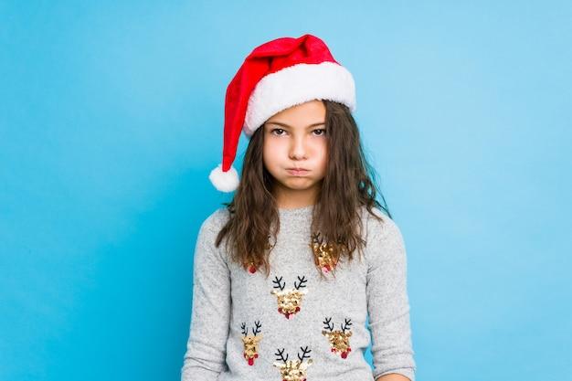 Mała dziewczynka świętuje boże narodzenie wieje policzki, ma zmęczony wyraz. koncepcja wyrazu twarzy. Premium Zdjęcia