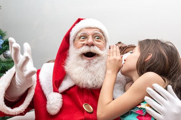Mała dziewczynka szepcze do ucha świętego mikołaja Premium Zdjęcia