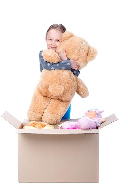 Mała Dziewczynka Trzyma Niedźwiedzia W Jej Rękach I Ono Uśmiecha Się. Premium Zdjęcia