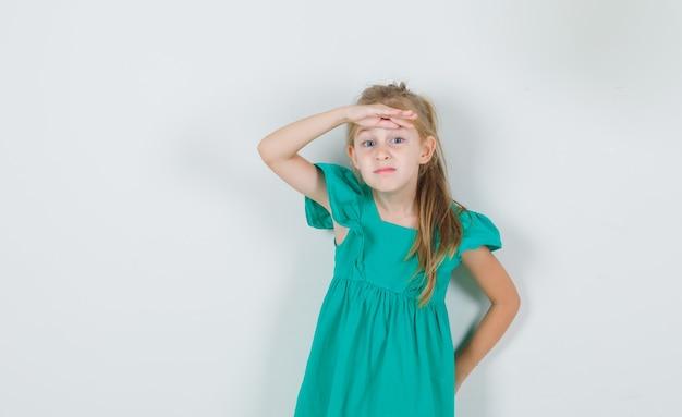Mała Dziewczynka Trzymając Rękę Na Oczy W Zielonej Sukience Darmowe Zdjęcia