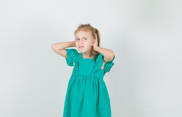 Mała Dziewczynka Trzymając Się Za Ręce Za Uszami W Zielonej Sukni I Niezadowolony. Przedni Widok. Darmowe Zdjęcia