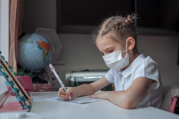 Mała Dziewczynka Uczy Się Medyczną Maskę Przy Odległości Domowym Szkoleniem Premium Zdjęcia