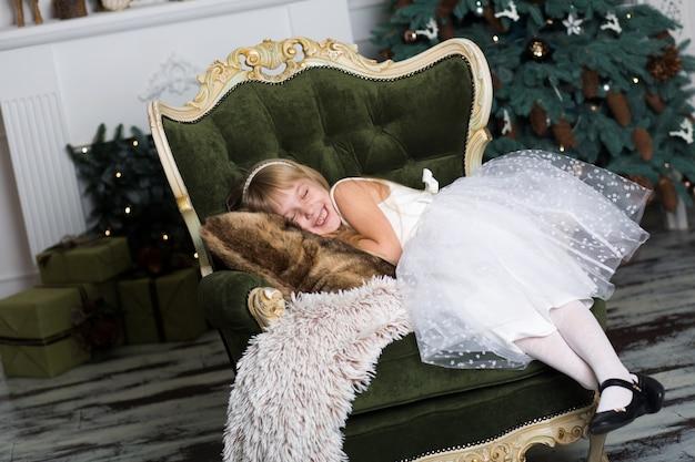 Mała Dziewczynka Udająca, że śpi Na Fotelu W Pobliżu Choinki, Aby Spotkać świętego Mikołaja, Gdy Przynosi Prezenty Premium Zdjęcia