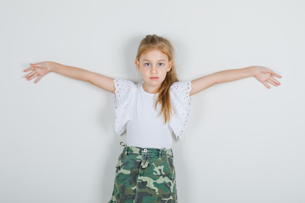 Mała Dziewczynka W Białej Koszulce, Spódnica Szeroko Otwierająca Ramiona I Wyglądająca Energicznie Darmowe Zdjęcia