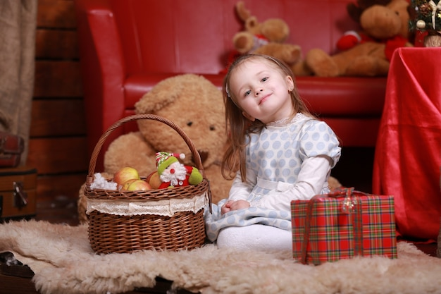 Mała Dziewczynka W Białej Sukience W Kropki, Zabawy W Studio Bożego Narodzenia. Z Przodu Choinka, Miś I Koszyczek Z Prezentami. Premium Zdjęcia