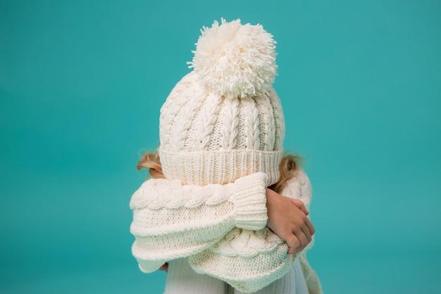 Mała Dziewczynka W Białej Zimowej Czapka I Sweter Na Niebiesko Premium Zdjęcia