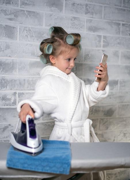 Mała Dziewczynka W Białym Płaszczu Z Lokówkami Na Głowie Na Jasnym Tle Trzyma Smartfon W Lewej Dłoni I Patrzy Na Nią, A W Prawej Trzyma żelazko Na Niebieskim Ręczniku. Pozycja Pionowa Premium Zdjęcia