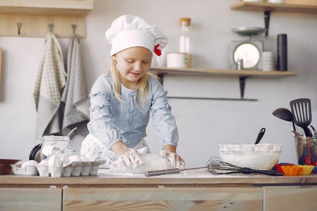 Mała dziewczynka w białym shef hat gotuje ciasto na ciastka Darmowe Zdjęcia