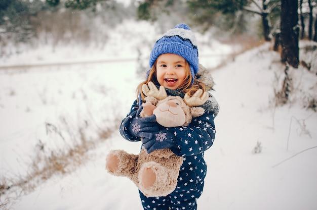 Mała dziewczynka w błękitnym kapeluszu bawić się w zima lesie Darmowe Zdjęcia