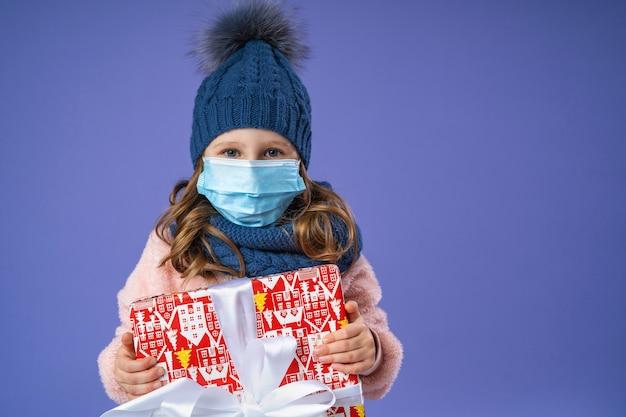Mała Dziewczynka W Czapce Z Dzianiny, Szaliku I Puszystym Swetrze Oraz Medycznej Masce Na Twarz W świątecznym Pudełku Na Fioletowo. Premium Zdjęcia
