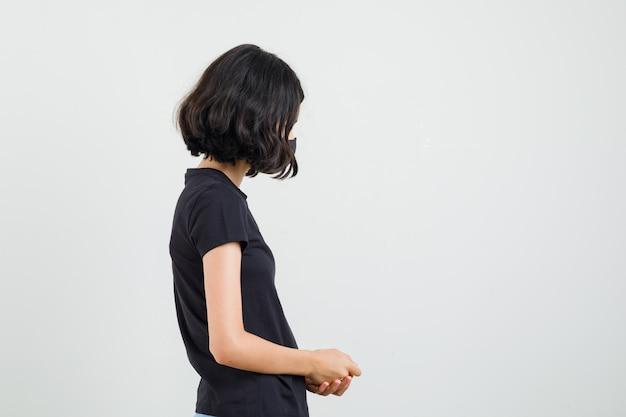 Mała Dziewczynka W Czarnej Koszulce, Maska Stojąca I Wyglądająca Spokojnie. Darmowe Zdjęcia
