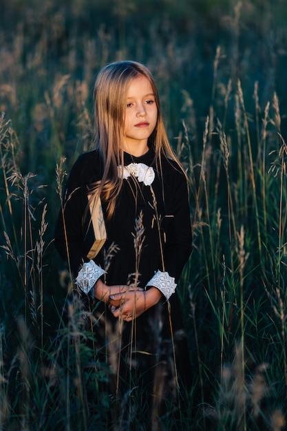Mała Dziewczynka W Czarnej Sukience Stoi W Wysokiej Trawie I Trzyma Zieloną Książkę, Patrząc Na Zachód Słońca. Premium Zdjęcia