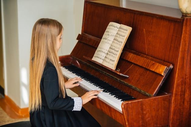 Mała Dziewczynka W Czarnej Sukience Uczy Się Grać Na Pianinie. Dziecko Gra Na Instrumencie Muzycznym. Premium Zdjęcia