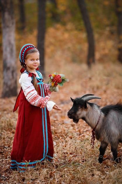 Mała Dziewczynka W Czerwonej Sukience Stoi Obok Czarnej Kozy W Jesiennym Lesie Premium Zdjęcia