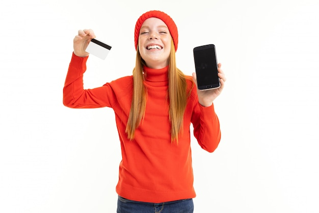 Mała Dziewczynka W Czerwonym Kapeluszu Cieszy Się Z Nowego Telefonu Z Kartą Kredytową W Ręku Premium Zdjęcia