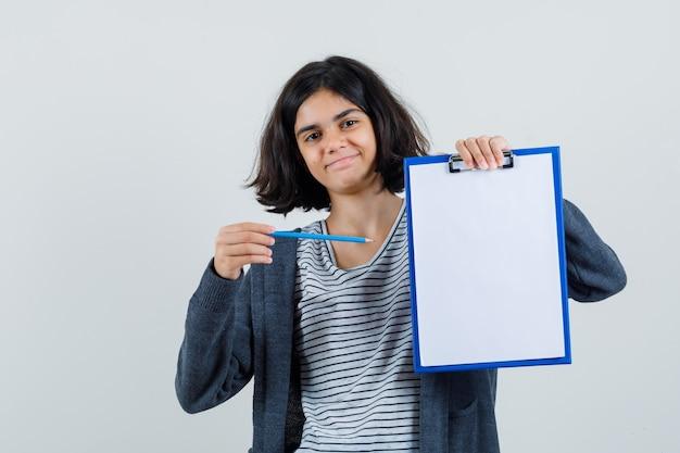 Mała Dziewczynka W Koszulce, Marynarka Wskazująca Ołówkiem Na Schowek I Wyglądająca Na Pewną Siebie, Darmowe Zdjęcia