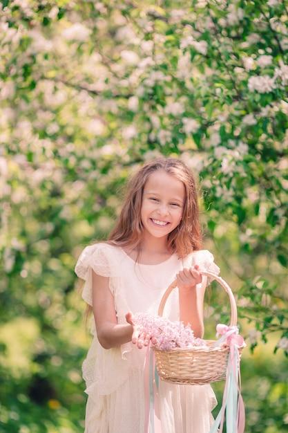 Mała dziewczynka w kwitnącym jabłko ogródzie na pięknym wiosna dniu Premium Zdjęcia