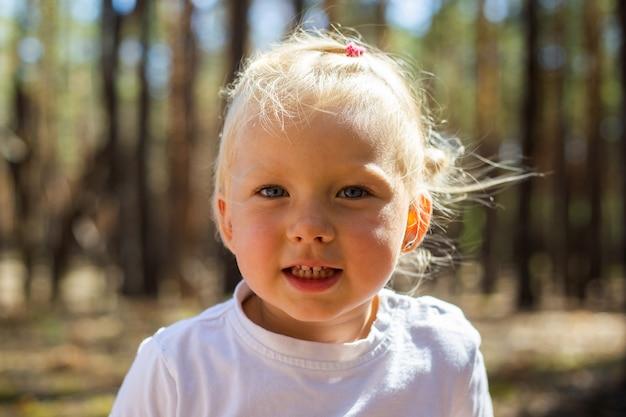 Mała Dziewczynka W Lesie. Spaceruj Z Rodzicami. Spacer Z Rodzicami. Premium Zdjęcia