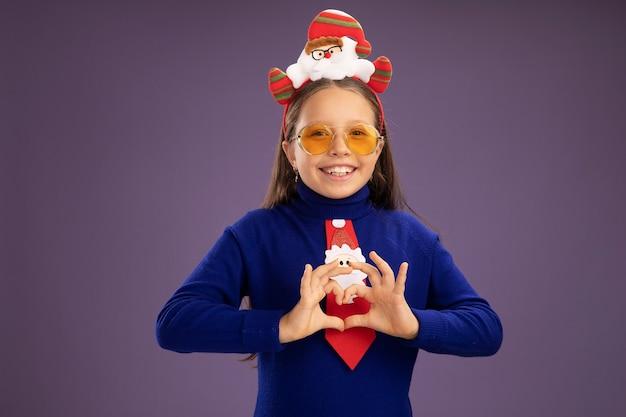 Mała Dziewczynka W Niebieskim Golfie Z Czerwonym Krawatem I Zabawną świąteczną Obwódką Na Głowie Patrząc W Kamerę Uśmiechnięta Wesoło, Wykonująca Gest Serca Palcami Stojącymi Na Fioletowym Tle Darmowe Zdjęcia