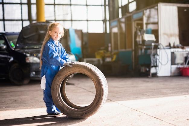 Mała Dziewczynka W Ogólnej Pozyci Z Samochodowym Kołem Darmowe Zdjęcia