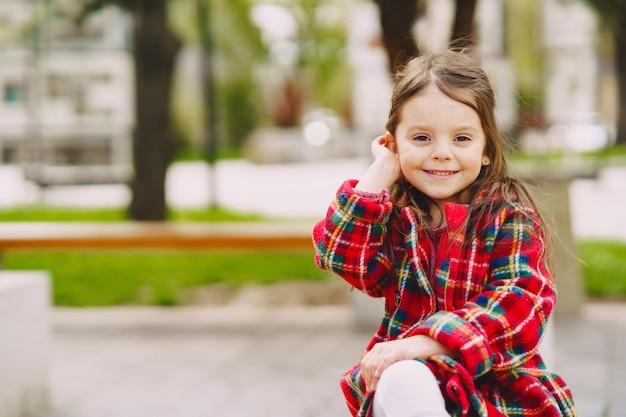 Mała Dziewczynka W Parkowym Obsiadaniu Na ławce Darmowe Zdjęcia