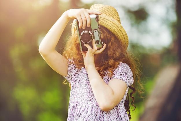Mała dziewczynka w słomkowym kapeluszu, wieśniak styl ubiera z retro fotografii kamerą w lato parku. Premium Zdjęcia