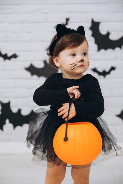 Mała Dziewczynka W Stroju Czarnego Kota Z Koszem Dyni Premium Zdjęcia