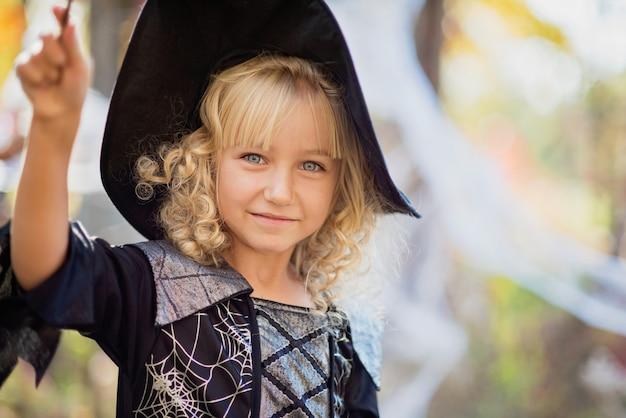 Mała Dziewczynka W Stroju Czarownicy świętuje Halloween Na Zewnątrz I Baw Się Dobrze. Premium Zdjęcia
