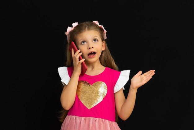 Mała Dziewczynka W Sukience Rozmawia Przez Telefon. Premium Zdjęcia