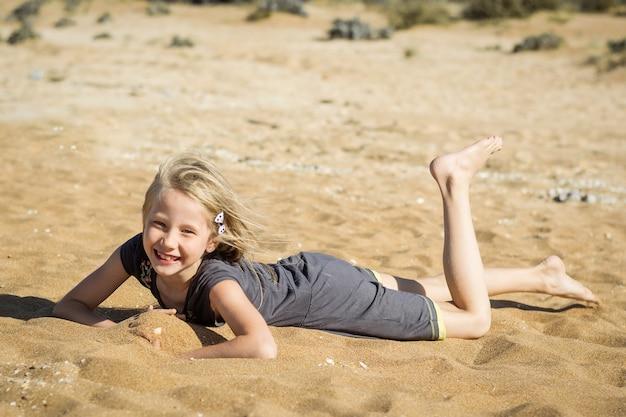 Mała dziewczynka w szarej sukience spoczywa na gorącym piasku. Premium Zdjęcia